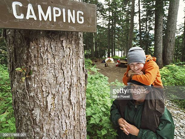 Son (7-11) sitting on fathers shoulders, standing by campground sign