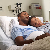 Son sleeps with father in hospial bed