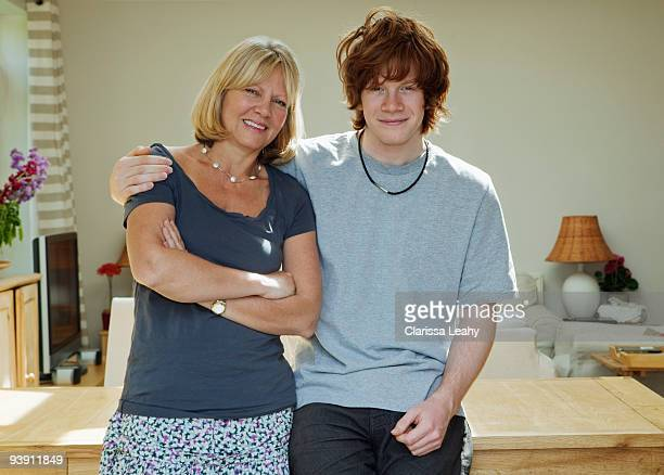 Son standing with arms around mother