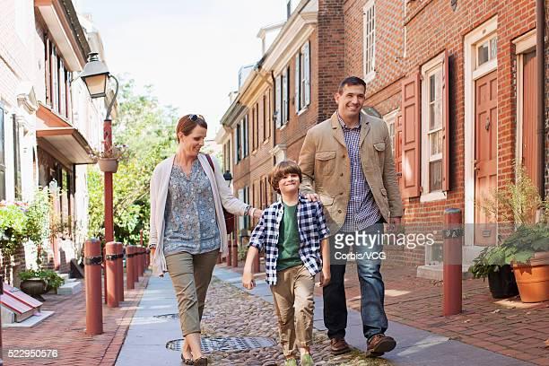 Son (8-9) walking with parents along town street, Philadelphia, Pennsylvania, USA