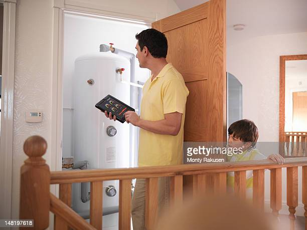 Son watching father check hot water tank with energy application on digital tablet