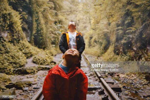 Son With Father Standing On Railroad Track In Forest