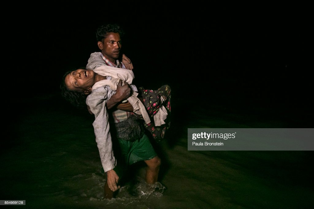 Sona Banu gets carried by Nobi Hossain to the shore of the Naf river as hundreds of Rohingya arrive by boats in the safety of darkness September 27, on Shah Porir Dwip island, Cox's Bazar, Bangladesh. Over 480,000 Rohingya refugees have fled into Bangladesh since late August during the outbreak of violence in Rakhine state as Myanmar's de facto leader Aung San Suu Kyi downplayed the crisis during a speech in Myanmar this week faces and defended the security forces while criticism on her handling of the Rohingya crisis grows. Bangladesh's prime minister, Sheikh Hasina, spoke at the United Nations General Assembly last week, focusing on the humanitarian challenges of hosting the minority Muslim group who currently lack food, medical services, and toilets, while new satellite images from Myanmar's Rakhine state continue to show smoke rising from Rohingya villages.