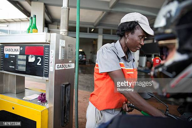 A Sonangol EP gas station attendant fills a vehicle with gasoline at a petrol pump in Luanda Angola on Wednesday Nov 6 2013 Angola the largest crude...