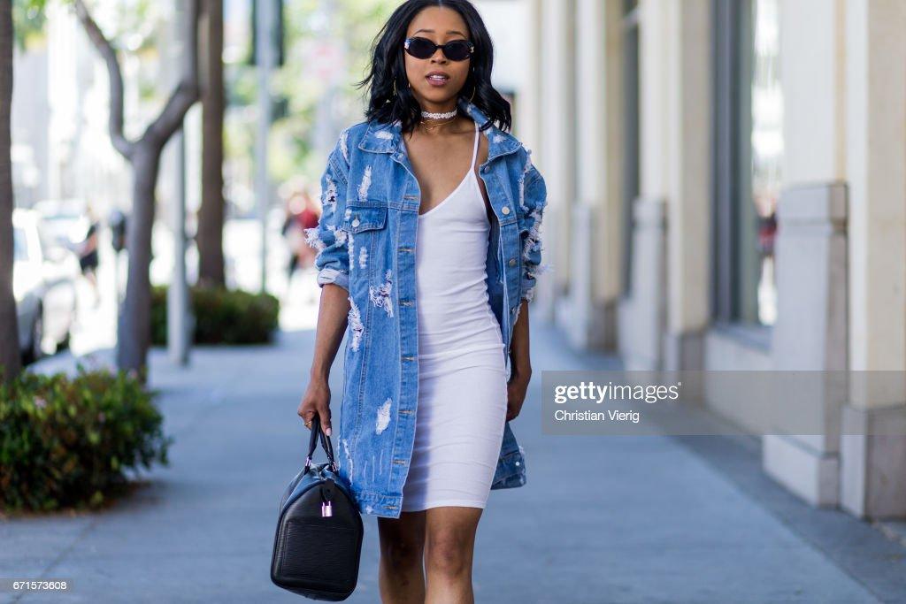 Sonaya wearing a denim jacket, white dress, Prada bag, sandals on April 21, 2017 in Los Angeles, California.