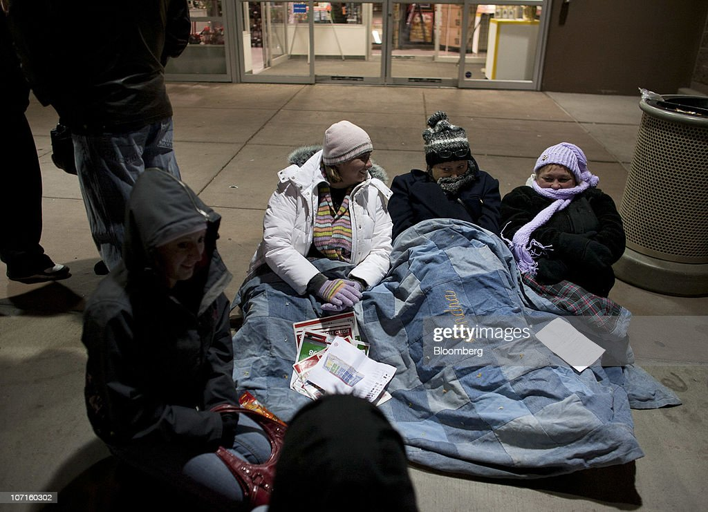 Sondra Brown, center left, Debra Anderson and Cathy Medina, right, and other shoppers wait in line before sunrise for the opening of a Super Target store in Thornton, Colorado, U.S., on Friday, Nov. 26, 2010. Shoppers on Black Friday, the biggest shopping day of the year, are taking advantage of deals as they face down a slower economic recovery than projected. Photographer: Matthew Staver/Bloomberg via Getty Images
