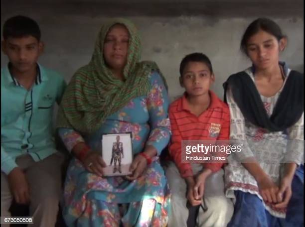 Sonepat martyr Naresh Kumar's wife Rajbala holding his picture along with their three children at Jainpur village on April 25 2017 in Sonepat India