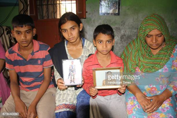 Sonepat martyr Naresh Kumar's wife Rajbala holding his picture along with their three children at Jainpur village on April 26 2017 in Sonepat India...