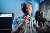 Musician in headphones recording his songs in studio