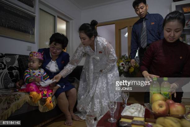 Song SongHui an eyeglass shop manager sits with her granddaughter as her family members prepare food in her apartment in Pyongyang on November 17...