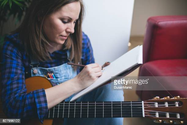 Songwriter Spaß Hobby Konzept und schreiben auf Briefbögen mit akustischer Gitarre in der Nähe von genießen. Musikinstrument lernen.