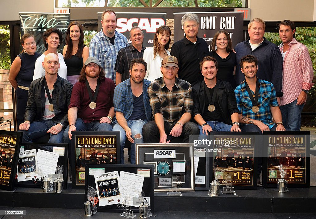 Songwriter Will Hoge (BMI) and Songwriter Eric Paslay (ASCAP)(center 1st. row) are honored for there #1 hit 'Even if it breaks your heart' recorded by Republic Nashville recording artists Eli Young Band, front row: Jon Jones, James Young, Mike Eli and Chris Thompson. Back Row: Back row (l-r): Cal IV Entertainment's Accounting & Office Manager Patricia Beal, Executive Assistant Lynn Woods, Administrative Assistant MaryAnn Keen, Director - Administration Brian Bradford, VP Creative Billy Lynn, Creative Manager Natalie Harker and President Daniel Hill; ASCAP's Director of Communications & Media Alison Toczylowski, Senior VP Creative Mike Sistad and Senior VP Creative Michael Martin at the CMA offices on August 20, 2012 in Nashville, Tennessee.