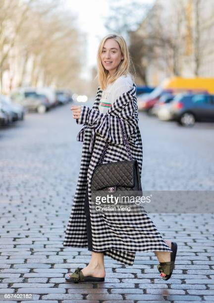 Sonia Lyson wearing a checked duster coat Topshop sandals with bow Topshop mother denim jeans Chanel bag on March 24 2017 in Berlin Germany