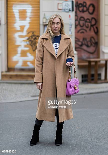 Sonia Lyson wearing black Lala Berlin velvet ankle boots black Levis pants a navy Rad sweater with print a beige Max Mara camel hair coat pink Gucci...