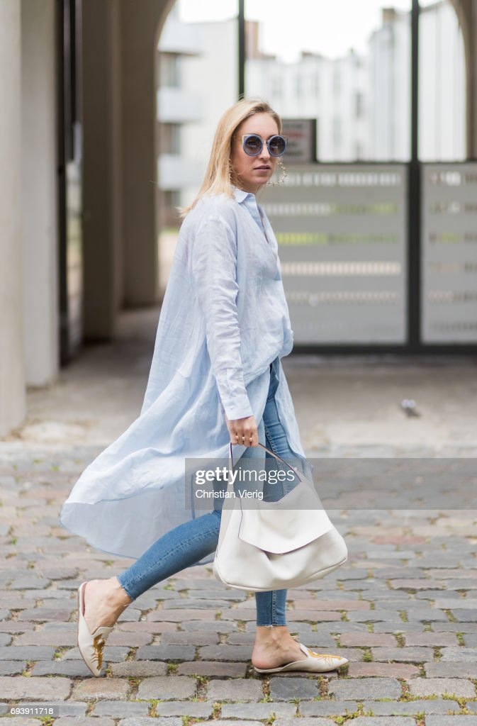 Sonia Lyson wearing Kurt Geiger shoes with lobster print, a blue oversized button shirt and denim jeans Zara, a vintage bag, Topshop hoop earings, erdem linda farrow sunglasses on June 8, 2017 in Berlin, Germany.