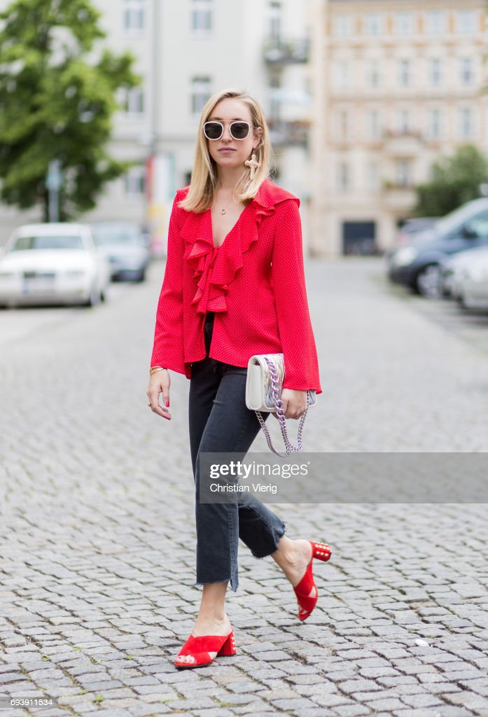 Sonia Lyson wearing red sandro slipper sandals Sandro, flared cropped denim jeans mother denim, red top topshop, Miu Miu bag, sunglasses &other stories, statement earings fawn star on June 8, 2017 in Berlin, Germany.