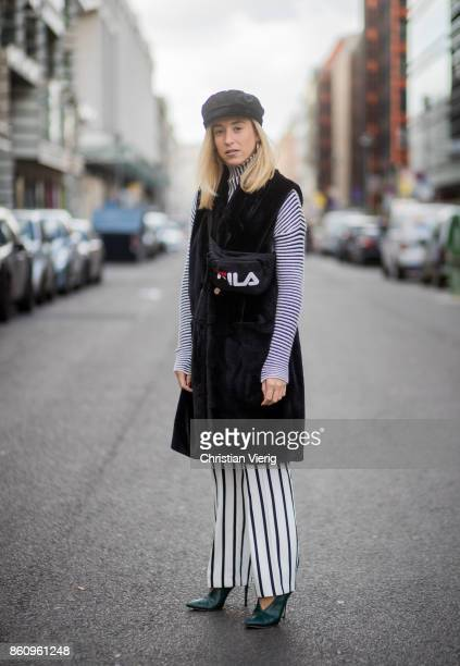 Sonia Lyson wearing shoes Jimmy Choo black white striped pants Topshop cropped turtleneck Longchamp black long fake fur vest Lala Berlin cap Zara...