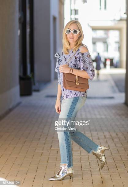 Sonia Lyson wearing silver Zara ankle boots HM Trend denim jeans a cut out stars top Sandro Valentino bag Acne sunglasses on March 24 2017 in Berlin...