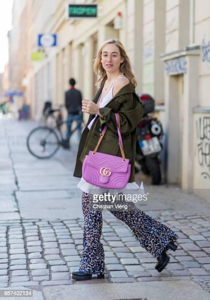 Sonia Lyson wearing Zara boots Ray Ban round glasses a green Lala Berlin parka animal print wide leg pants Lala Berlin pink Gucci bag on March 24...
