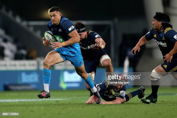 Sonny Bill Williams of the Blues breaks the tackle of Elliot Dixon and Joe Wheeler of the Highlanders during the round seven Super Rugby match...