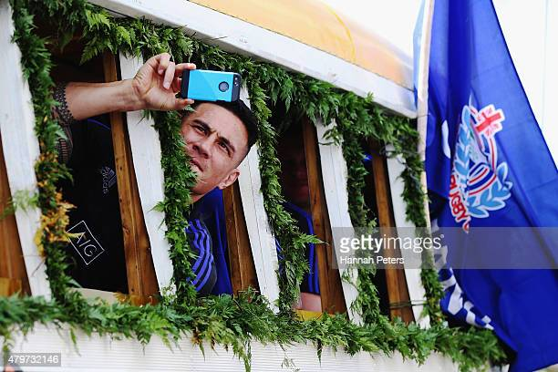 Sonny Bill Williams of the New Zealand All Blacks takes photos during a parade down the main street of Apia on July 7 2015 in Apia Samoa