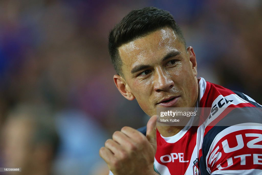 Sonny Bill Williams of the Roosters smiles as he watches on from the bench during the NRL Preliminary Final match between the Sydney Roosters and the Newcastle Knights at Allianz Stadium on September 28, 2013 in Sydney, Australia.
