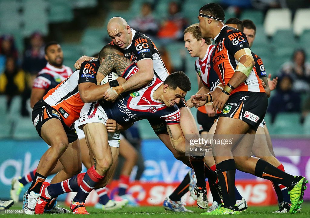 <a gi-track='captionPersonalityLinkClicked' href=/galleries/search?phrase=Sonny+Bill+Williams&family=editorial&specificpeople=204424 ng-click='$event.stopPropagation()'>Sonny Bill Williams</a> of the Roosters struggles with the defence during the round 23 NRL match between the Wests Tigers and the Sydney Roosters at Allianz Stadium on August 19, 2013 in Sydney, Australia.