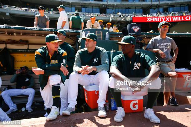 Sonny Gray Andrew Triggs and Jharel Cotton of the Oakland Athletics talk in the dugout during the game against the Washington Nationals at the...
