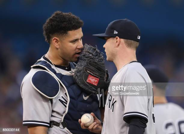 Sonny Gray of the New York Yankees talks to Gary Sanchez on the mound in the third inning during MLB game action against the Toronto Blue Jays at...