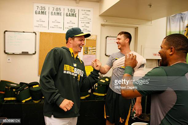 Sonny Gray of the Oakland Athletics celebrates with Scott Kazmir and Alberto Callaspo in the clubhouse following the game against the Toronto Blue...
