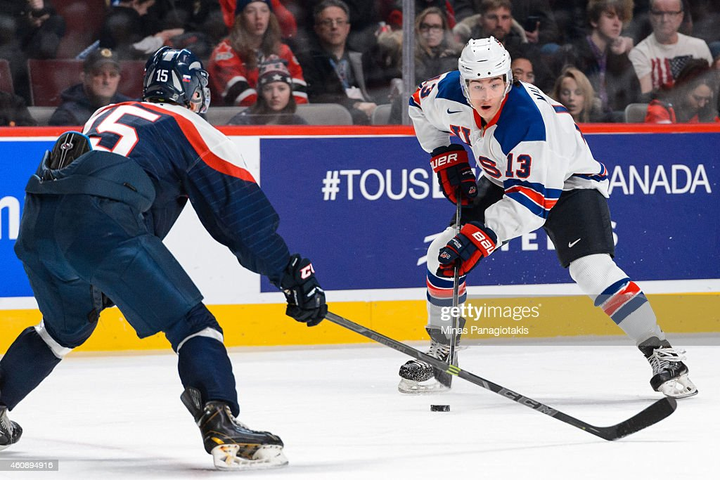 Sonny Milano #13 of Team United States looks to play the puck near Patrik Bacik #15 of Team Slovakia during the 2015 IIHF World Junior Hockey Championship game at the Bell Centre on December 29, 2014 in Montreal, Quebec, Canada. Team United States defeated Team Slovakia 3-0.