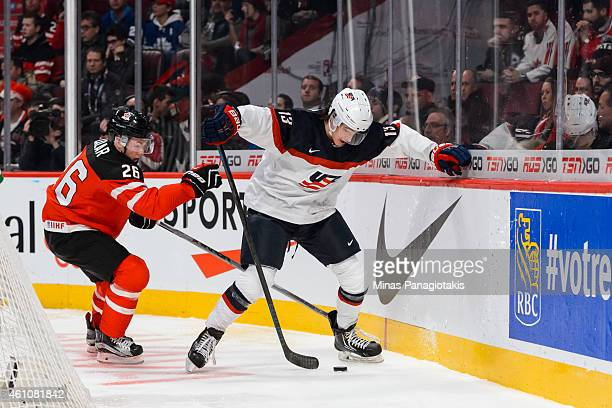 Sonny Milano of Team United States tries to play the puck against the boards with Curtis Lazar of Team Canada close by in a preliminary round game at...