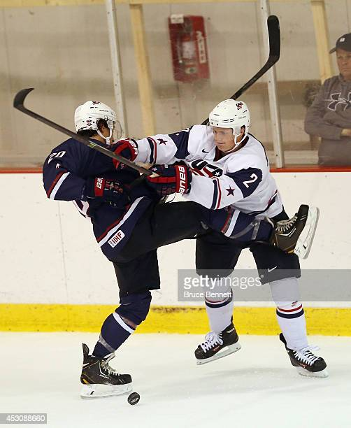 Sonny Milano of USA Blue is hit by Mike Brodzinski of USA White during the 2014 USA Hockey Junior Evaluation Camp at Lake Placid Olympic Center on...