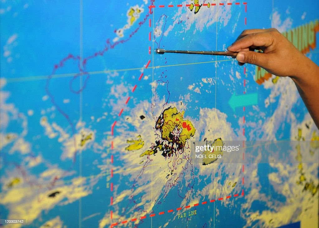 Sonny Pajarilla, a Philippine weather forecaster points to a satellite image showing the position of Tropical storm Nock-ten during a media briefing at the weather bureau's office in Manila on July 26, 2011. One person drowned while thousands fled their flooded homes as a tropical storm hit the Philippines, causing heavy rains and rough seas that disrupted aviation and shipping, officials said.