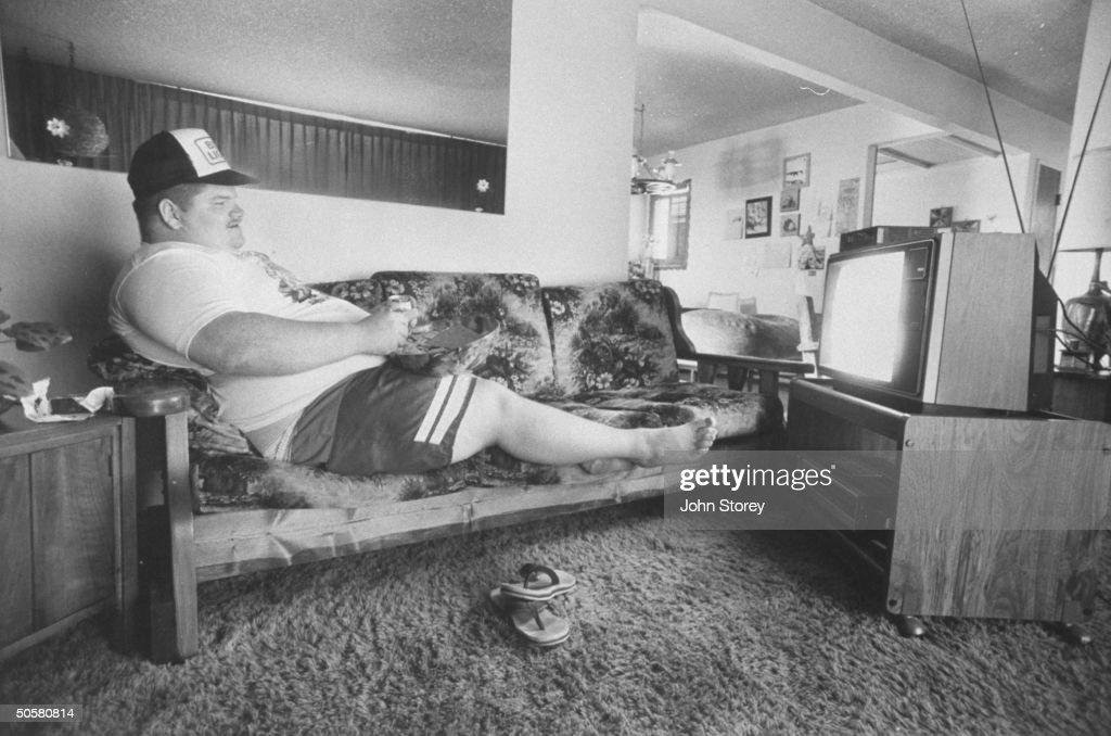 Sonoma County fair couch potato runner-up, Dean Houghton watching TV in prone position while eating junk food.