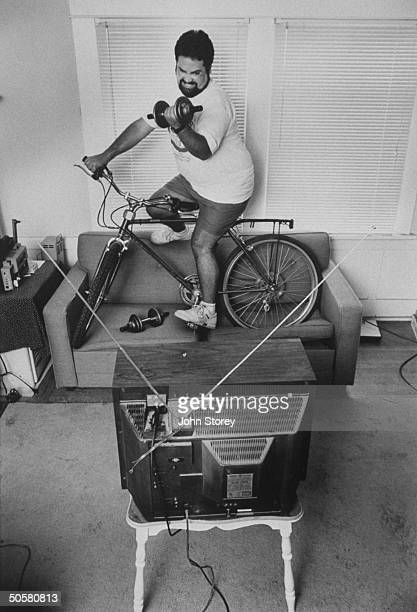 Sonoma County fair couch potato winner John Silveira lifting weight while riding bike on couch watching TV at home