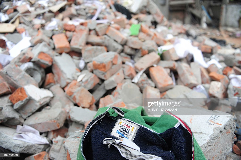 A S & D, Sons and Daughters clothing item lies in the rubble after a eight-storey building collapsed in Savar, on the outskirts of Dhaka, on April 30, 2013. Bangladesh on Tuesday defended its decision to snub foreign aid after the collapse of a factory complex as anger flared at the recovery operation and towards the building's owner when he appeared in court with the death toll from the country's worst ever industrial disaster now standing at 387. AFP PHOTO/MUNIR UZ ZAMAN