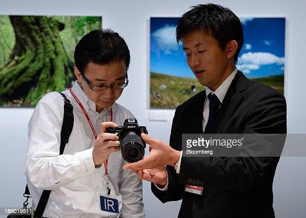 A Sony Corp employee right demonstrates the A7 mirrorless digital camera to an attendee at an unveiling in Tokyo Japan on Wednesday Oct 16 2013 Sony...
