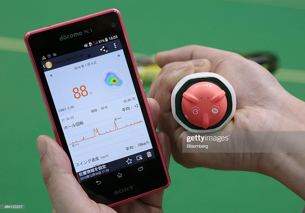 Sony Corp.'s Smart Tennis Sensor device, attached to the end of a tennis racket, is arranged for a photograph with a Sony smartphone displaying an app that tracks the data collected by the sensor in Tokyo, Japan, on Monday, Jan. 20, 2014. The development of wearable technology such as eyeglasses, watches and earpieces is expanding as consumers seek new ways to integrate computers into everyday life. Photographer: Yuriko Nakao/Bloomberg via Getty Images