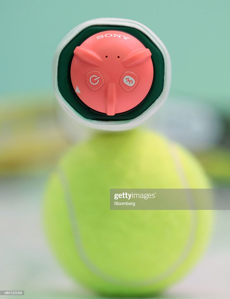 Sony Corp.'s Smart Tennis Sensor device, attached to the end of a tennis racket, is arranged for a photograph atop a tennis ball in Tokyo, Japan, on Monday, Jan. 20, 2014. The development of wearable technology such as eyeglasses, watches and earpieces is expanding as consumers seek new ways to integrate computers into everyday life. Photographer: Yuriko Nakao/Bloomberg via Getty Images