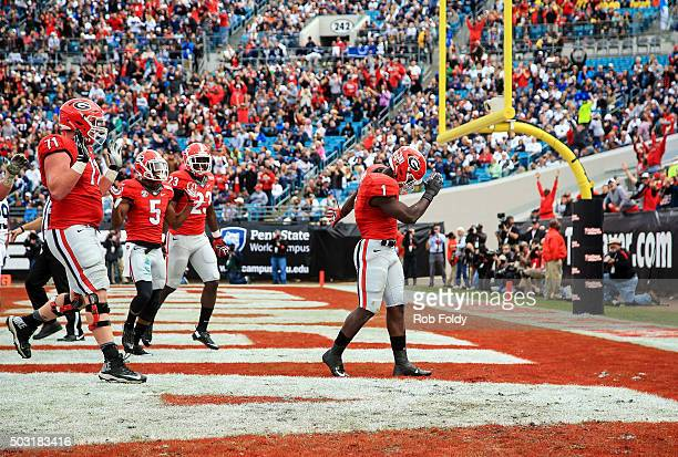 Sony Michel of the Georgia Bulldogs gestures after scoring a touchdown during the second half of the TaxSlayer Bowl game against the Penn State...