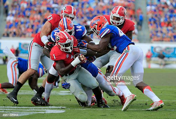 Sony Michel of the Georgia Bulldogs is tackled by Alex McCalister of the Florida Gators during the game at EverBank Field on October 31 2015 in...
