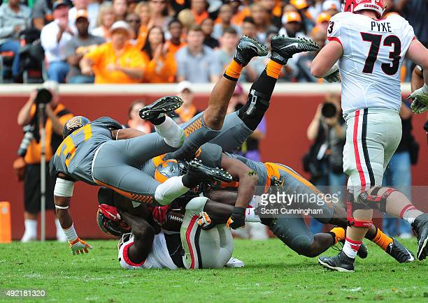 Sony Michel of the Georgia Bulldogs is tackled by Jalen ReevesMaybin Brian Randolph and Derek Barnett of the Tennessee Volunteers on October 10 2015...