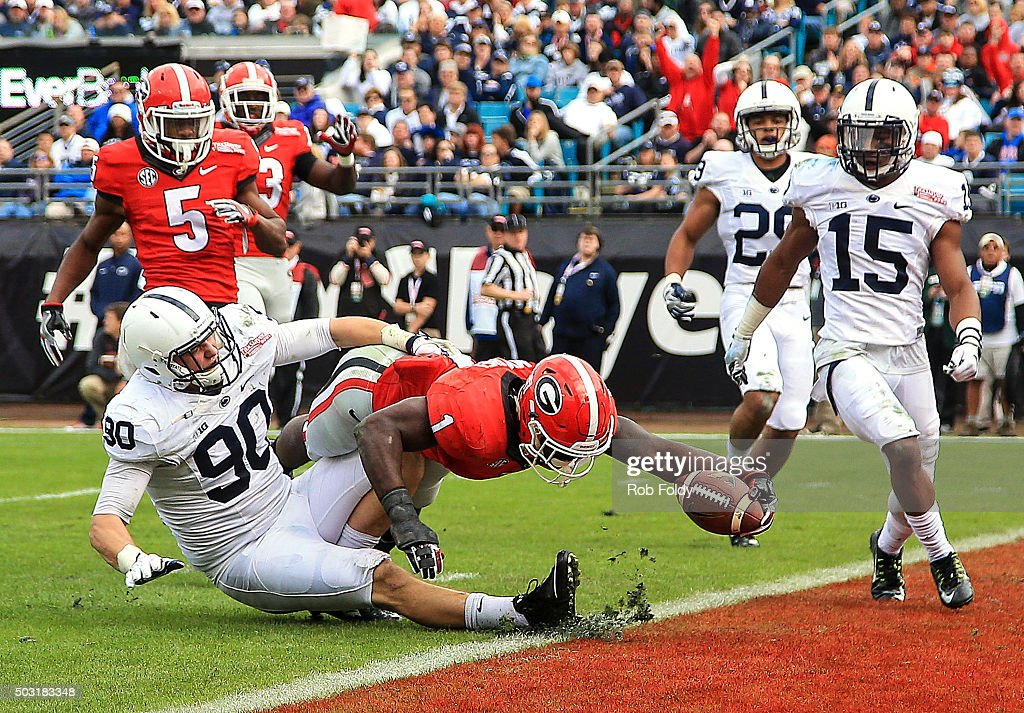 Sony Michel of the Georgia Bulldogs reaches past Garrett Sickels of the Penn State Nittany Lions to score a touchdown during the second half of the...