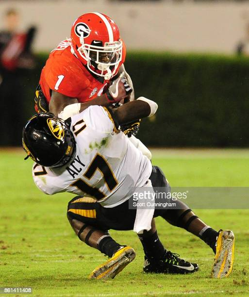 Sony Michel of the Georgia Bulldogs runs over DeMarkus Acy of the Missouri Tigers at Sanford Stadium on October 14 2017 in Athens Georgia
