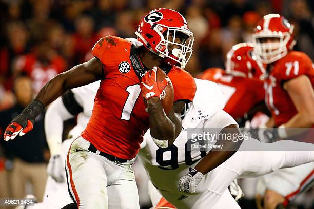 Sony Michel of the Georgia Bulldogs runs the ball past Darrius Sapp of the Georgia Southern Eagles during the first half at Sanford Stadium on...