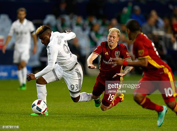 Sony Mustivar of Sporting Kansas City controls the ball as Luke Mulholland of Real Salt Lake falls to the ground during the Major League Soccer match...