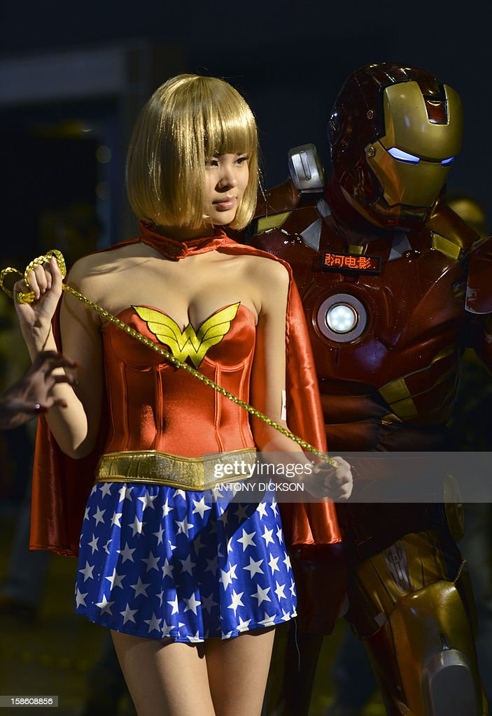 A Sony Playstation promotional girl dressed as Wonder Woman (L) poses for a picture next to Iron Man during the Asia Game Show (AGS) in Hong Kong on December 21, 2012. The AGS is highlighting products from the electronic gaming industry and runs from December 21 to 24. AFP PHOTO / Antony DICKSON