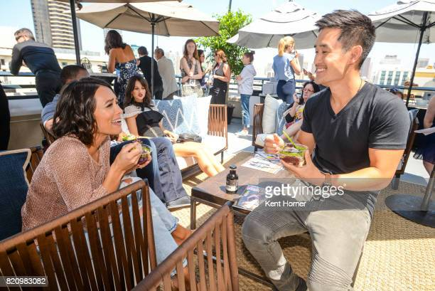 Sonya Balmores and Mike Moh enjoying a Sambazon Acai Bowl in the EW Studio at San Diego Comic Con on July 20 2017 in San Diego California