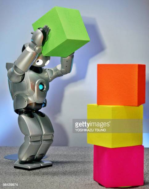 Sony's humanoid robot QRIO places a polystyrene cube on a target point for a demonstration of his ability at the Sony building in Tokyo 16 December...
